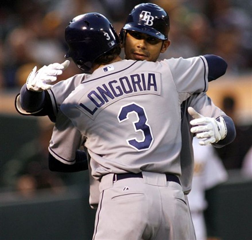 The Tampa Bay Rays' Carlos Pena gets a hug from Evan Longoria after his two-run home run against the Oakland Athletics  in the fourth inning of an MLB baseball game, Thursday, Aug. 19, 2010 in Oakland, Calif. (AP Photo/Dino Vournas)