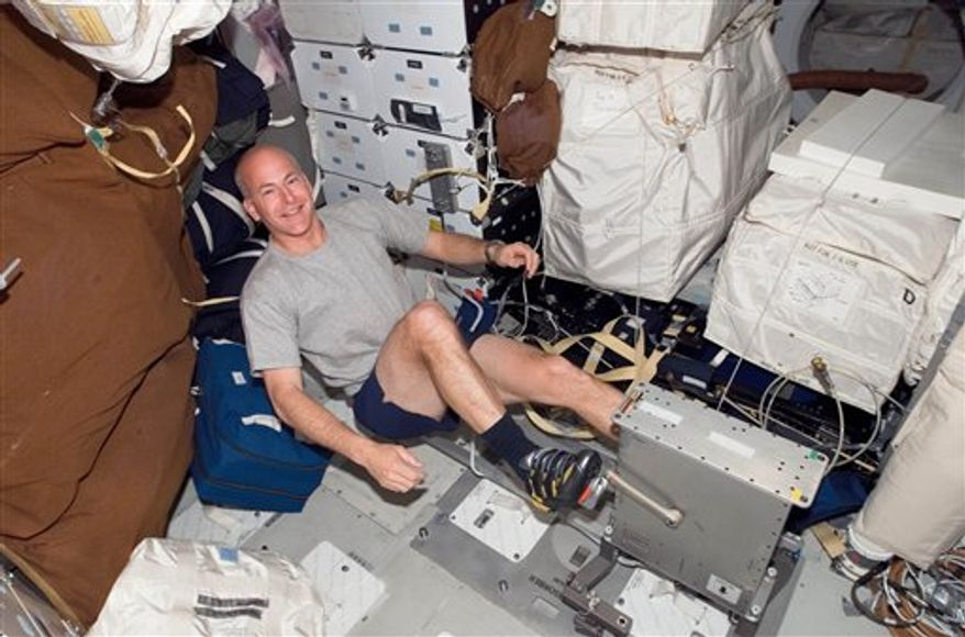 FILE - This Thursday, Feb. 14, 2008 image provided by NASA shows astronaut Alan Poindexter exercising on a bicycle ergometer on the space shuttle Atlantis while docked with the International Space Station. Astronauts can become as weak as 80-year-olds after six months at the International Space Station, according to a new study that raises serious health concerns as NASA contemplates prolonged trips to asteroids and Mars. (AP Photo/NASA)