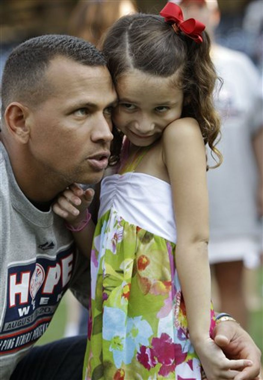 New York Yankees third baseman Alex Rodriguez is shown holding his daughter Natasha on the field during a Yankees HOPE week baseball game after the Yankees regular baseball game against the Detroit Tigers at Yankee Stadium in New York, Thursday, Aug. 19, 2010. (AP Photo/Kathy Willens)