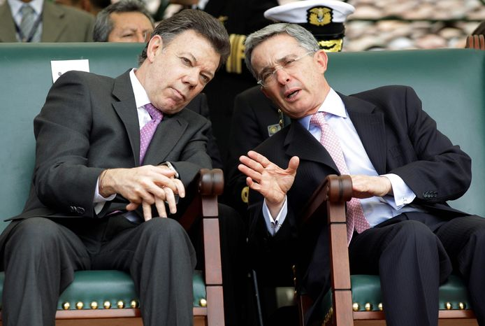 Colombian President Alvaro Uribe speaks to President-elect Juan Manuel Santos (left) during a military ceremony in Bogota, Colombia, on Aug. 6. Mr. Santos was inaugurated as Colombia's president, succeeding Mr. Uribe. (Associated Press)