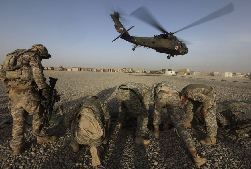U.S. soldiers shield themselves from the rotor wash of a medevac helicopter as it takes off with patients in the Zhari district of Kandahar province in southern Afghanistan on Friday, Aug. 20, 2010. (AP Photo/Brennan Linsley)
