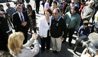 Australian Prime Minister Julia Gillard, leader of the Labor Party, poses for a photo with an unidentified man in her hometown of Altona in Melbourne, Australia, on Sunday, Aug. 22, 2010. It could take more than a week to learn who will govern Australia after a cliffhanger election, the closest in nearly 50 years, and the winner may have to woo the support of a handful of independent lawmakers in order to assume power. (AP Photo/Andrew Brownbill)
