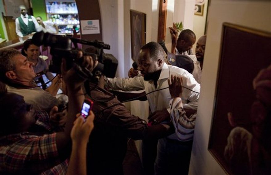 Haitian-born singer and presidential candidate Wyclef Jean, right, exits a hotel room after Haiti's Electoral Council rejected his presidential candidacy in Port-au-Prince, Haiti, Friday, Aug. 20, 2010. The council's spokesman Richard Dumel announced Friday that it has accepted 19 presidential candidacies and has rejected 15 others for the upcoming Nov. 28 presidential election, including Jean's because he did not meet the residency requirement of having lived in Haiti for five years before election. (AP Photo/Ramon Espinosa)