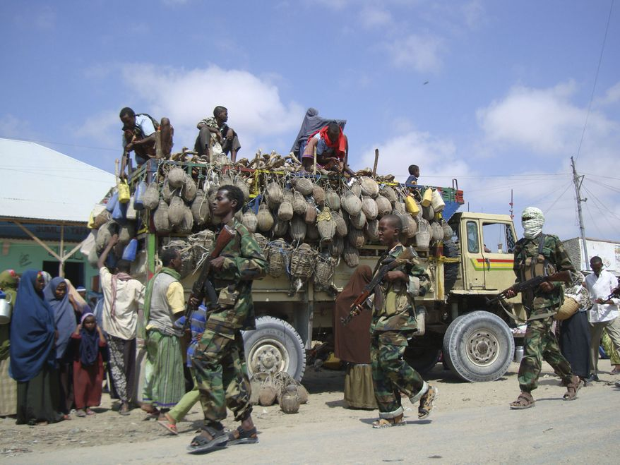 ** FILE ** Hard-line Islamist al-Shabab fighters conduct a military exercise in the northern Suqaholaha  neighborhood of the Somali capital, Mogadishu. Al-Shabab, which is linked to al Qaeda, is reported to have started ordering parents in the country's south to give a boy from every household to the militants to boost the militia's ranks. Childless families are being forced to pay the militants $50 a month. (AP Photo/Farah Abdi Warsameh, File)