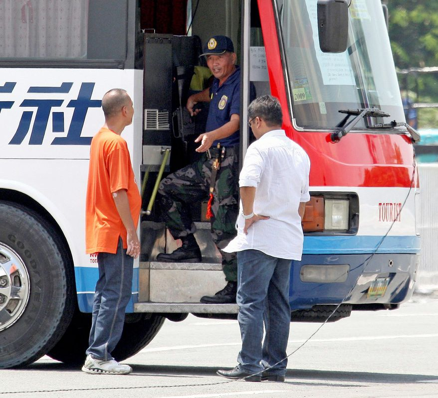 Rolando Mendoza, a dismissed police officer, talks to negotiators during a standoff where he held hostages in a tour bus. Mendoza was later killed after he wounded a police sharpshooter. (Associated Press)