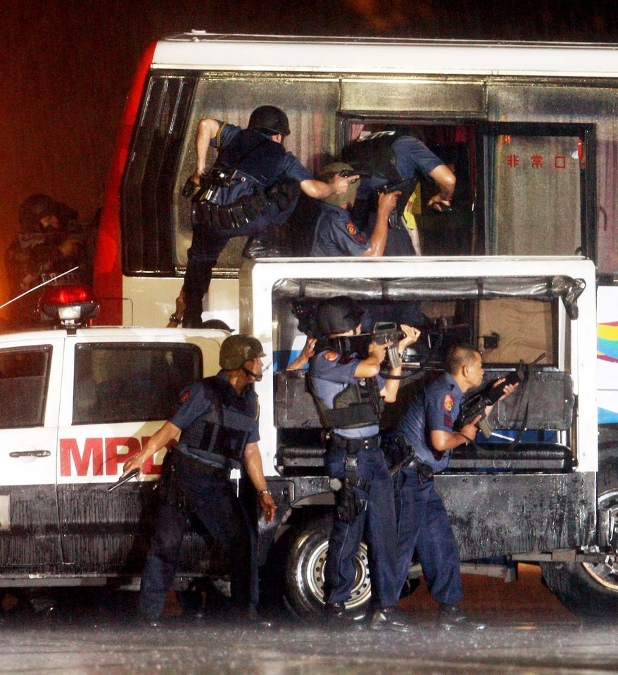 Police and SWAT members rush a tourist bus to rescue hostages on Monday in Manila, Philippines. Rolando Mendoza, an ex-policeman armed with an automatic rifle, seized the bus and demanded reinstatement. (Associated Press)