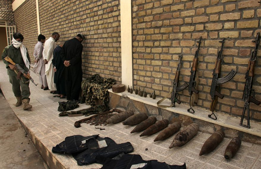 An Afghan soldier stands guard over arrested Taliban suspects and confiscated arms and ammunition at a police compound in Herat, west of Kabul, Afghanistan, on Monday, Aug. 23, 2010. (AP Photo/Reza Shirmohammadi)