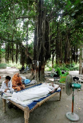 A sick Pakistani's bed sits outside Tuesday for lack of room at a rural health center in a flood-affected district of Punjab province. Hundreds of health facilities have been damaged by flooding. (Associated Press)