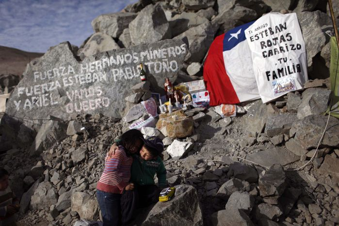 """Elias Sepulveda (right) embraces her cousin Katherine on Monday, Aug. 23, 2010, in front of a tribute site with candles, flags and messages for their relatives Esteban and Pablo Rojas, two of the 33 miners trapped at the collapsed mine in Copiapo, Chile. The message at top left reads: """"Be strong brother miners, be strong Esteban, Pablo, Tono and Ariel. Let's go Queero."""" At right, the message says, """"We love you Esteban Rojas Carrizo, your family."""" (AP Photo/Roberto Candia)"""