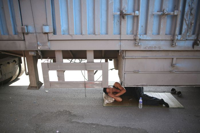 In this photo taken Monday, Aug. 23, 2010, a driver takes a nap under his truck jammed on an entrance ramp to the Beijing-Tibet Highway in Guoleizhuang township, in north China's Hebei province. The massive traffic jam that stretches for dozens of miles and hit its 10-day mark on Tuesday stems from road construction in Beijing that won't be finished until the middle of next month, an official said. (AP Photo)