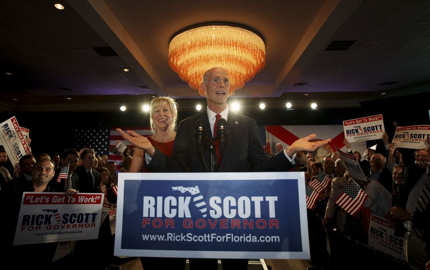 Republican gubernatorial candidate Rick Scott (center) gestures as he speaks with supporters on Tuesday, Aug. 24, 2010, in Fort Lauderdale, Fla. At left is Mr. Scott's wife, Ann. Florida's GOP voters chose the wealthy Mr. Scott, a political newcomer, over career public servant Bill McCollum as their candidate for governor. (AP Photo)