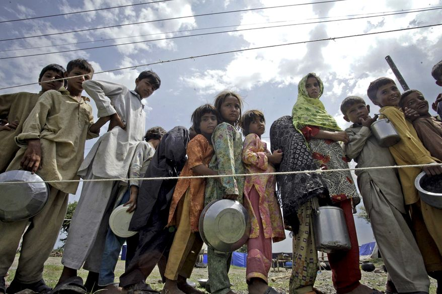 Pakistani flood victims line up for food in a camp set up for displaced people in Nowshera, Pakistan, on Tuesday, Aug. 24, 2010. Recovering from the devastating floods still battering Pakistan will take at least three years, President Asif Ali Zardari said Monday, as the waters swept south after leaving millions homeless and submerging millions of acres of farmland. (AP Photo/Mohammad Sajjad)