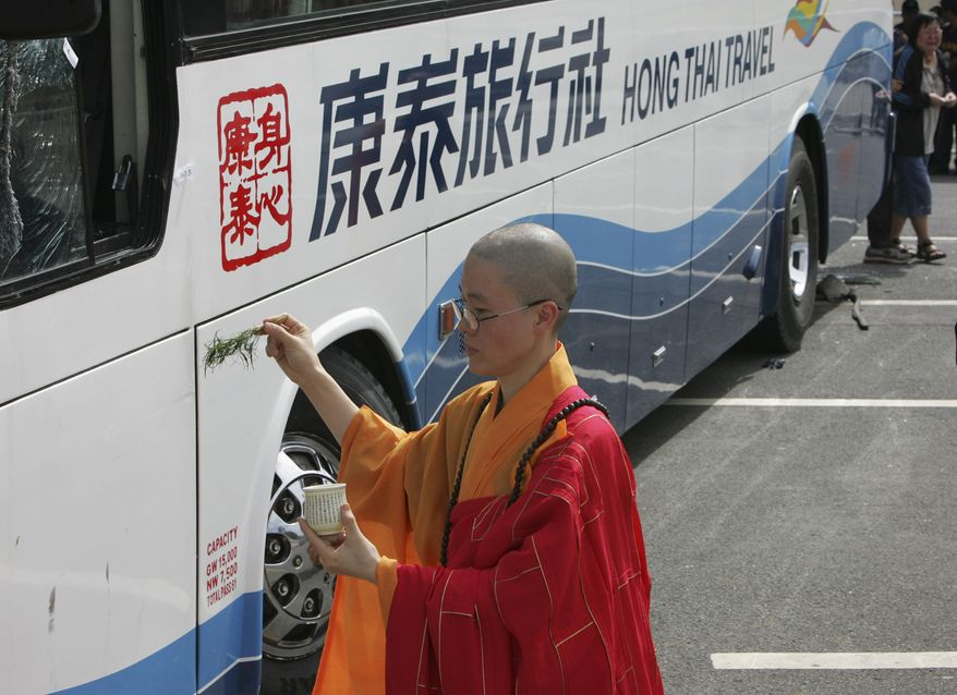 A Buddhist monk sprinkles holy water at the bullet-riddled tourist bus during a ceremony to mourn the eight Hong Kong tourists who were killed in the hostage crisis Tuesday Aug.24, 2010 at Rizal Park in Manila, Philippines. The Chinese authorities demanded answers from the Philippines on Tuesday after a 12-hour hostage drama in the heart of Manila ended with eight Hong Kong tourists and their Filipino hostage-taker dead following a day of botched negotiations. (AP Photo/Bullit Marquez)