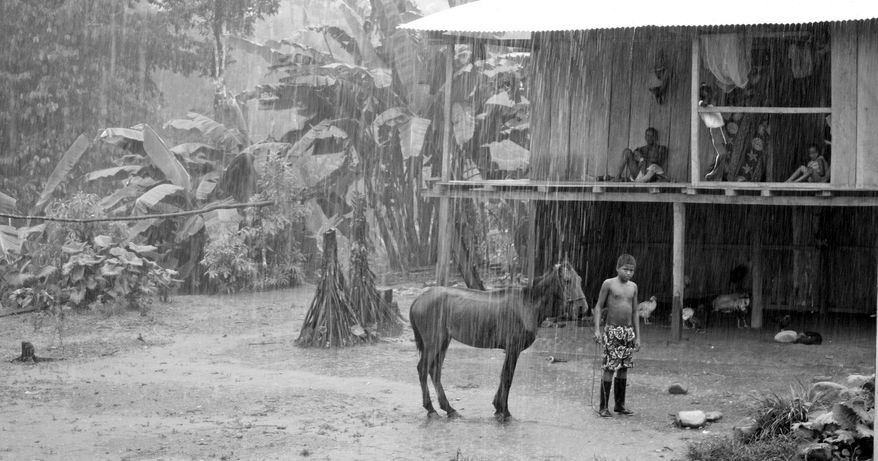 A young boy stands in a rainstorm in the refugee village of Providencia on Ecuador's San Miguel River. Residents of Providencia say Ecuadorean soldiers came to their homes, asking questions, and later were targeted as Colombian guerrilla collaborators. (Kelly Hearn)