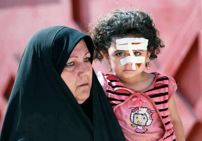 An Iraqi girl wears bandages after being injured in a bombing in Karbala, 50 miles south of Baghdad, on Wednesday. The car bomb near a police station wounded 28 people. (Associated Press)