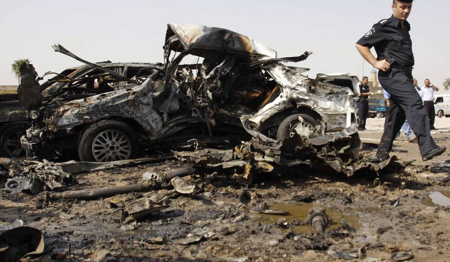An Iraqi policeman walks past a destroyed car at the site of a bombing in Basra, Iraq's second-largest city, 340 miles southeast of Baghdad, Iraq, Wednesday, Aug. 25, 2010. A string of attacks targeting Iraqi security forces on Wednesday left several people dead and scores wounded, police and hospital officials said the day after the number of American soldiers in the country fell bellow 50,000.(AP Photo/Nabil al-Jurani)