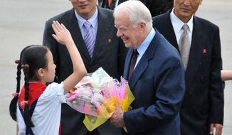 In this photo released by China's Xinhua News Agency, a child salutes former U.S. President Jimmy Carter, center, upon his arrival at the airport in Pyongyang, North Korea, on Wednesday, Aug. 25, 2010. Carter arrived in North Korea on Wednesday on a mission U.S. officials said was aimed at bringing home an imprisoned American. (AP Photo/Xinhua, Yao Ximeng)
