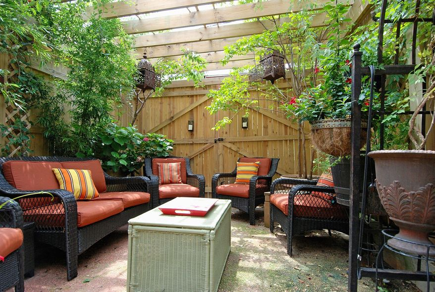 The owners have created a private double patio in the backyard. One section is covered with a trellis and foliage.