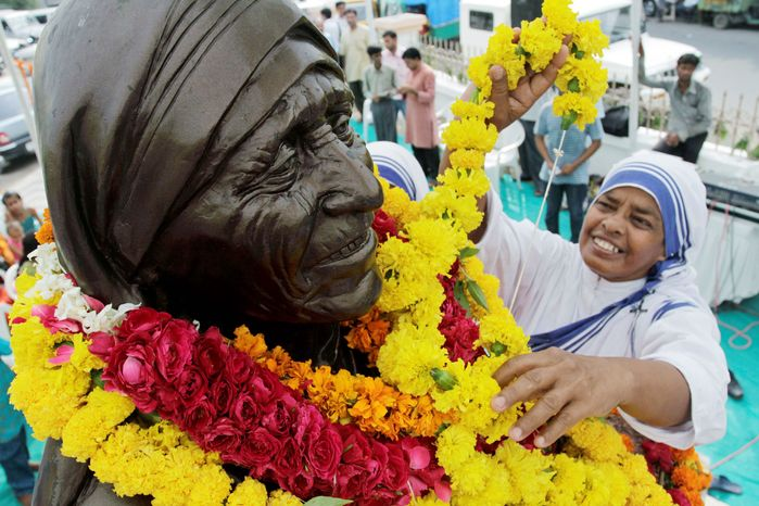 ASSOCIATED PRESS PHOTOGRAPHS A sister of the Missionaries of Charity decorates a bust of Mother Teresa, the order's founder, during celebrations in Ahmadabad, India, marking her birth centenary on Thursday. Celebrations were planned across India and around the world.