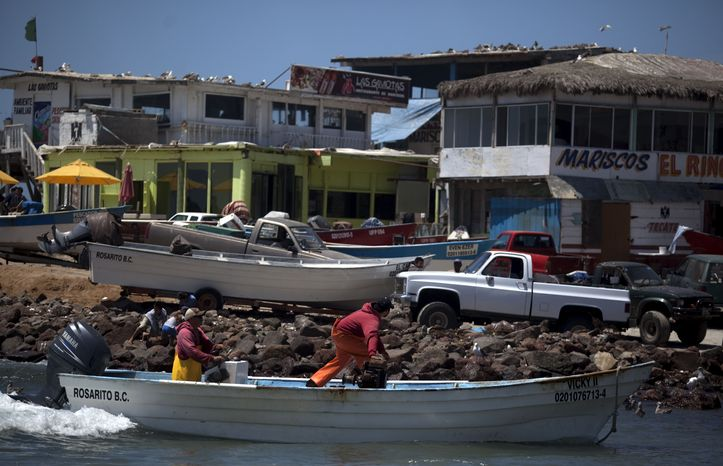 Fishermen arrive on shore in the fishing village of Popotla, Mexico, some 15 miles south of the U.S.-Mexico border, on July 14, 2010. Gambling their lives, illegal immigrants increasingly are looking to the ocean, as they consider crossing overland even more arduous and more likely to end in getting caught. U.S. agents have arrested 753 suspected illegal immigrants on Southern California shores and seas since October. (AP Photo/Guillermo Arias)