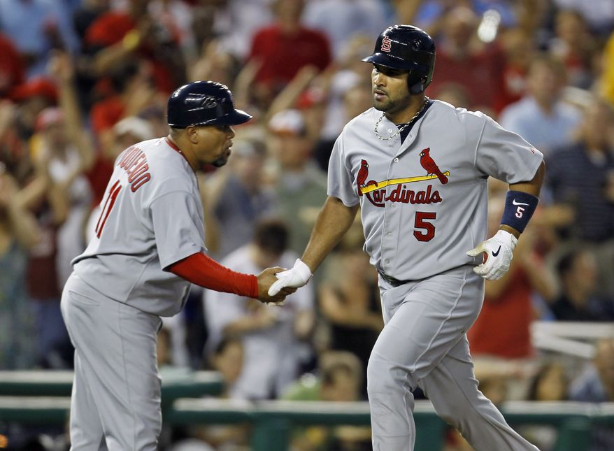 ASSOCIATED PRESS St. Louis Cardinals' Albert Pujols is congratulated by third base coach Jose Oquendo as he runs the bases after hitting his 400th home run in the fourth inning of a baseball game with the Washington Nationals at Nationals Park in Washington Thursday, Aug. 26, 2010.