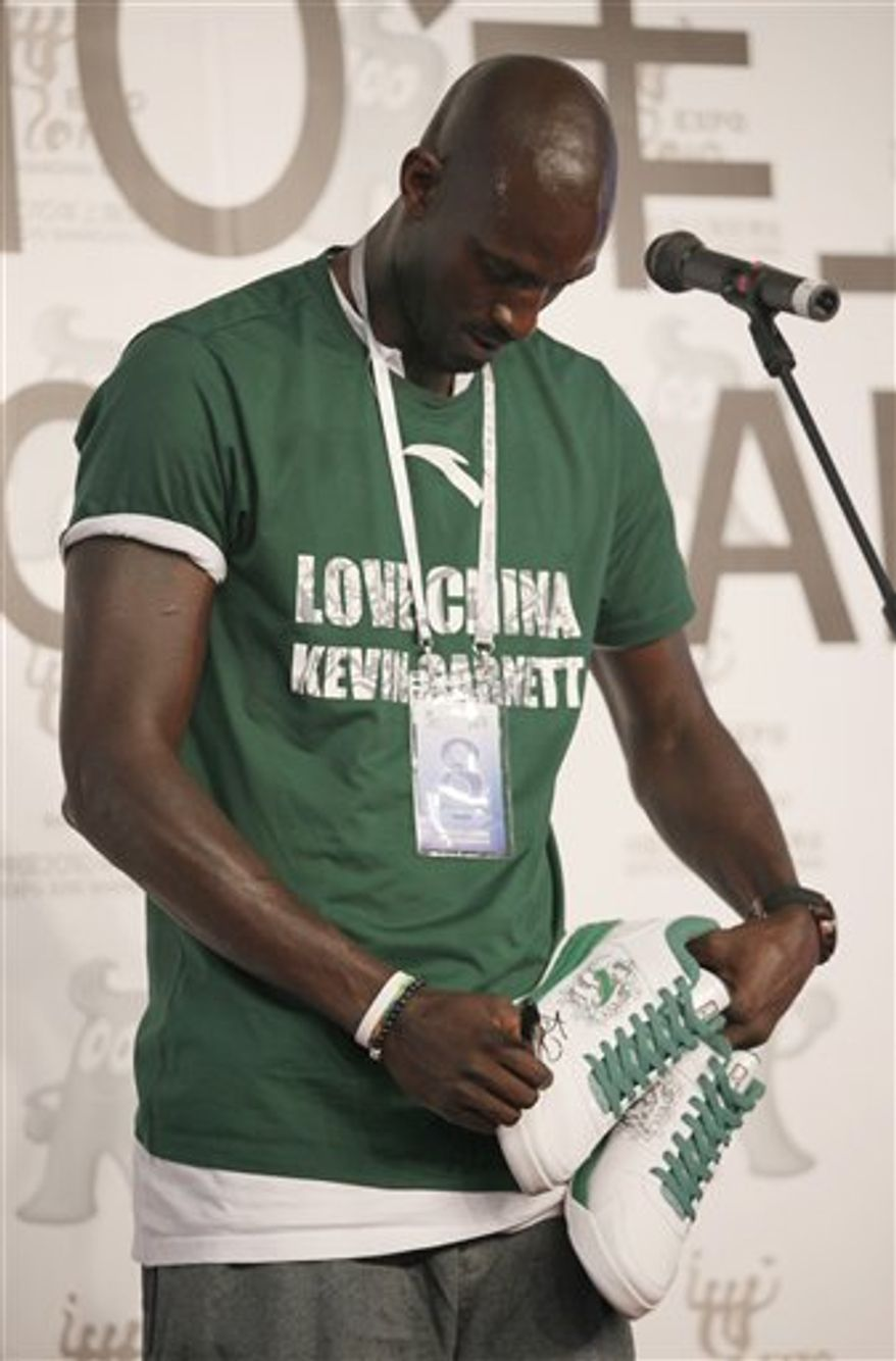 In this photo taken Thursday, Aug. 5, 2010,  NBA's Boston Celtics power forward Kevin Garnett, second left, attends promotional event of Anta in Shanghai. Garnett wore his affection for China's booming sportswear market arrived in Beijing. On the front of his T shirt: The angular red slash logo of Anta, the athletic shoe producer that brought Garnett to China for a weeklong promotional tour. To reach worldly young Chinese consumers, the country's new but ambitious brands are scouring the globe for athletes, film stars and other celebrity spokespeople like Garnett who might have no personal link to China but are stars here. (AP Photo)