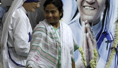 Indian Railway Minister Mamata Banerjee gestures as Head of the Missionaries of Charity Sister Mary Prema, left, looks on during the inauguration of a special exhibition train on Mother Teresa, portrait seen, marking her birth centenary in Calcutta, India, Thursday, Aug. 26, 2010. (AP Photo/Bikas Das)