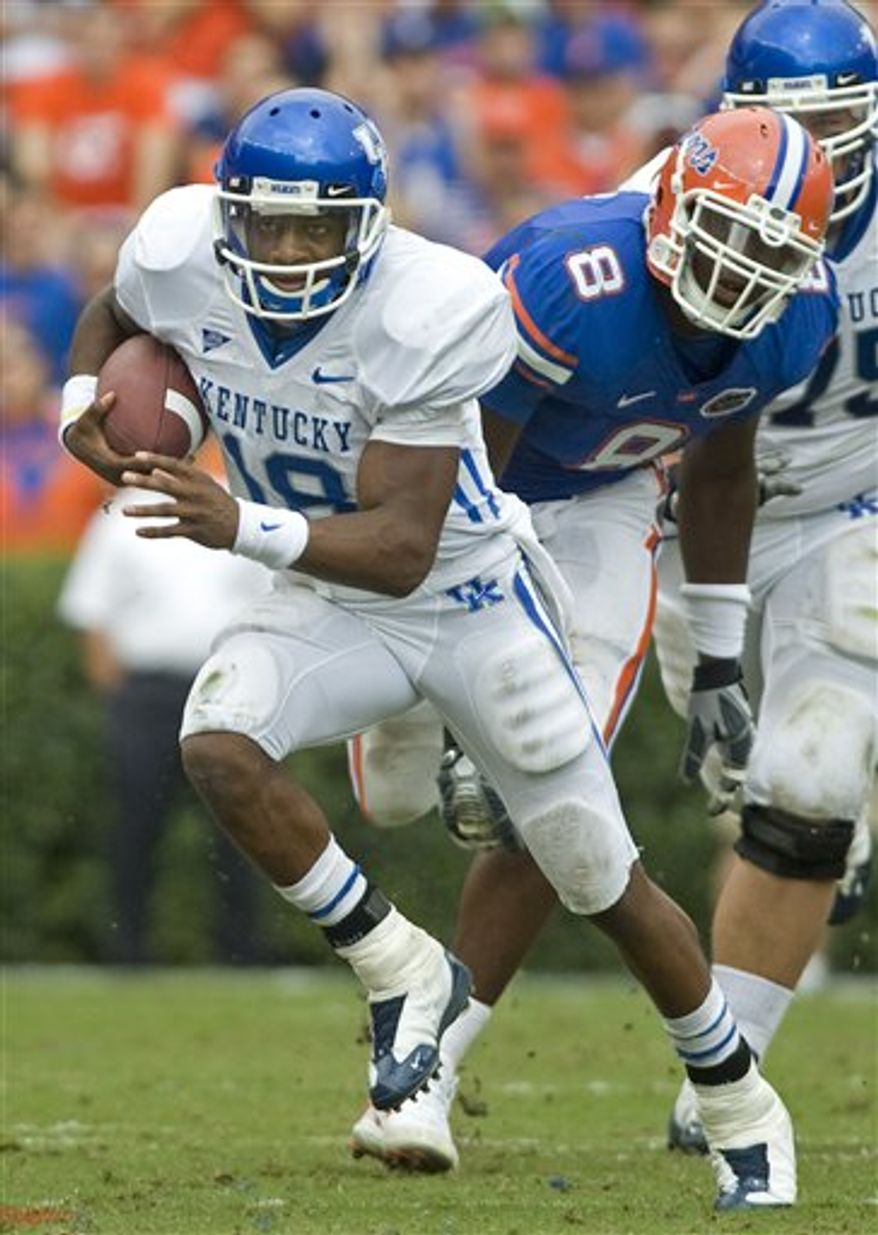 This photo taken Oct. 25, 2008 shows Kentucky  quarterback Randall Cobb (18) gaining ground with Florida's defensive end Carlos Dunlap (8) unable to stop during  NCAA college football play in Gainesville, Fl.  (AP Photo/Phil Sandlin)