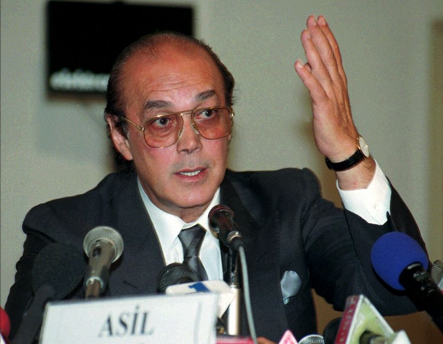 In this Friday, May 30, 1997, file picture Asil Nadir, the former chairman of food and electronics conglomerate Polly Peck, gestures during a press conference in Istanbul,Turkey. The tycoon who fled Britain almost two decades ago following the spectacular collapse of his business empire told British media Thursday that he is returning to London to face charges of fraud. (AP Photo/Murad Sezer/File)