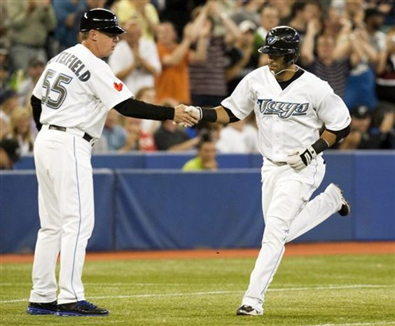 Toronto Blue Jays Jose Bautista, right, is congratulated by third base coach Brian Butterfield after hitting a home run off New York Yankees starting pitcher Ivan Nova during third inning of a baseball game in Toronto on Monday Aug. 23, 2010. (AP Photo/The Canadian Press, Frank Gunn)