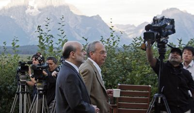 Federal Reserve chairman Ben Bernanke, left, and Donald L. Kohn, governor of the Federal Reserve Bank of Dallas, walk along the veranda of the Jackson Lake Lodge with the Grand Tetons in the distance, Friday, Aug. 27, 2010, at the start of the annual Federal Reserve conference in Jackson, Wyo. (AP Photo/Reed Saxon)