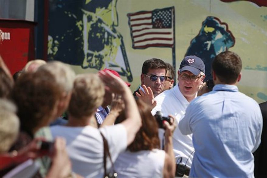 Glenn Beck, right, waves to supporters at the site of the Restoring Honor rally by the Lincoln Memorial in Washington, on Friday, Aug. 27, 2010.  The rally will take place on Saturday.  Image in the rear is an artist rendition of Astronaut Buzz Aldrin from the Apollo 11 mission to the moon. (AP Photo/Jacquelyn Martin)