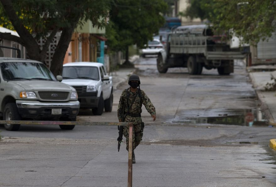 A navy officer guards a street where a funeral home is holding the bodies of 72 men and women that were purportedly killed by the Zetas drug gang are in San Fernando, just 100 miles from the the Mexican border with the U.S. near the city of Matamoros, Mexico, Thursday Aug. 26, 2010. A wounded migrant who escaped the Zetas gang stumbled into a military checkpoint and led marines to the scene were migrants from Brazil, Ecuador, El Salvador and Honduras were executed. (AP Photo/Guillermo Arias)