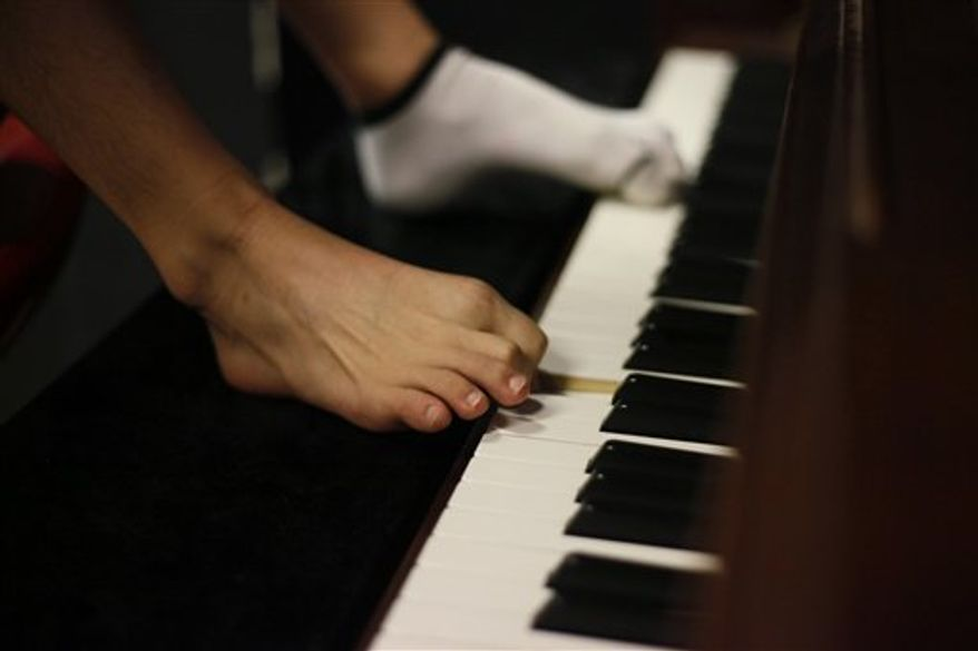 "In this Aug. 26, 2010 photo, pianist Liu Wei plays the piano with his toes during his practice session in Shanghai.   The 23-year-old, whose arms were amputated after a childhood accident, plays the piano with his toes.  Liu was thrust into the limelight earlier this month when he performed on ""China's Got Talent,"" the Chinese version of the TV show that helped make Britain's Susan Boyle a singing star. (AP Photo/Eugene Hoshiko)"