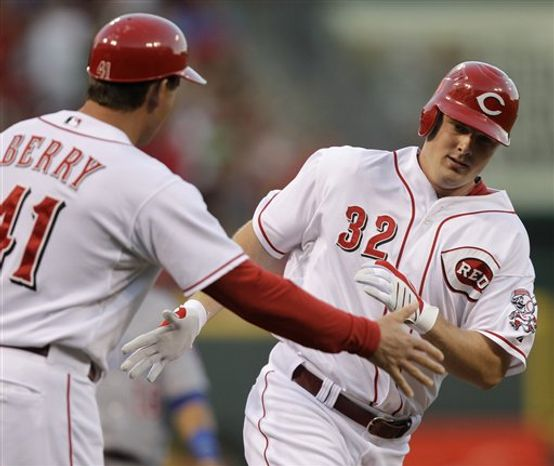 Cincinnati Reds' Jay Bruce (32) is congratulated by third base coach Mark Berry after hitting a solo home run off Chicago Cubs starting pitcher Tom Gorzelanny in the third inning of a baseball game, Friday, Aug. 27, 2010, in Cincinnati. (AP Photo/Al Behrman)