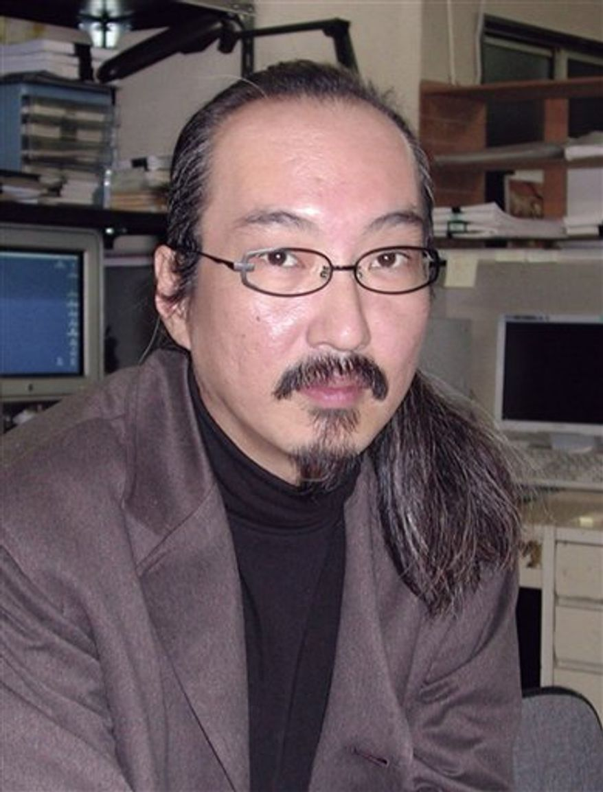 """In this photo taken in 2003, Japanese animation film director Satoshi Kon sits in his office in Tokyo. Kon, known for """"Tokyo Godfathers,"""" """"Millennium Actress,"""" and other prize-winning films, died of pancreas cancer Tuesday, Aug. 25, 2010. He was 46. (AP Photo/Kyodo News)"""