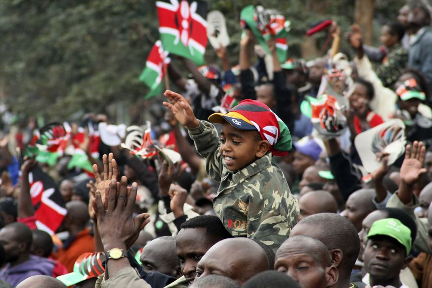 A young boy reacts as Kenyans watch the signing of the new constitution into law, at Uhuru Park in Nairobi, Kenya, Friday, Aug. 27, 2010. African leaders including indicted Sudanese President Omar Bashir joined tens of thousands of Kenyans Friday as a new constitution was signed into law that institutes an American-style system of checks and balances on power. (AP Photo/Sayyid Azim)