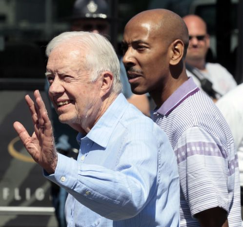 ** FILE ** Former President Jimmy Carter (left) waves to onlookers after arriving at Boston's Logan International Airport with Aijalon Gomes (right) on Aug. 27, 2010. Mr. Carter flew to the North Korean capital, Pyongyang, on a private mission to secure a pardon for the 31-year-old Mr. Gomes, an American who was detained in January after crossing into the country from China. (AP Photo/Winslow Townson)