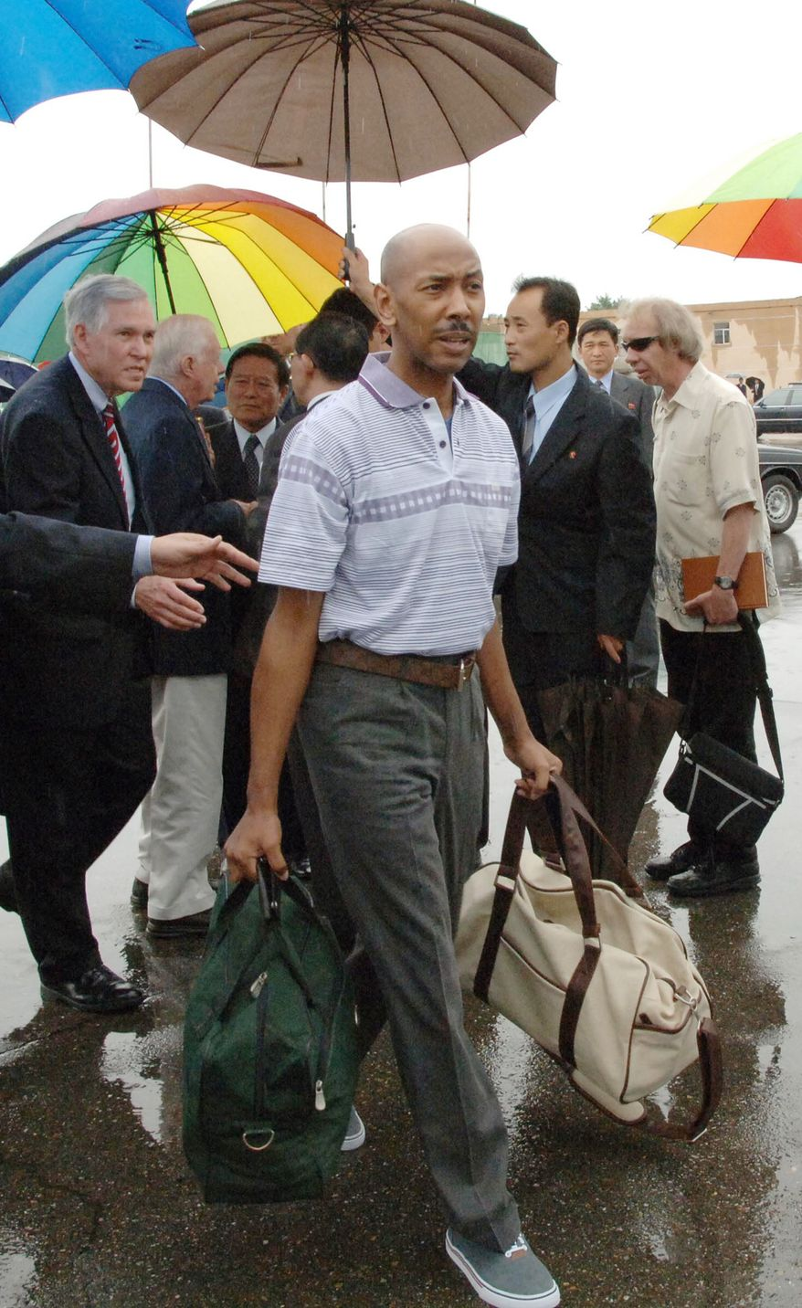 American Aijalon Gomes, center, prepares to leave North Korea from Pyongyang airport, on Friday, Aug, 27, 2010. Mr. Gomes, freed after nearly seven months jailed in North Korea, left Pyongyang on Friday in the company of the former President Jimmy Carter. (AP Photo/Kyodo News)