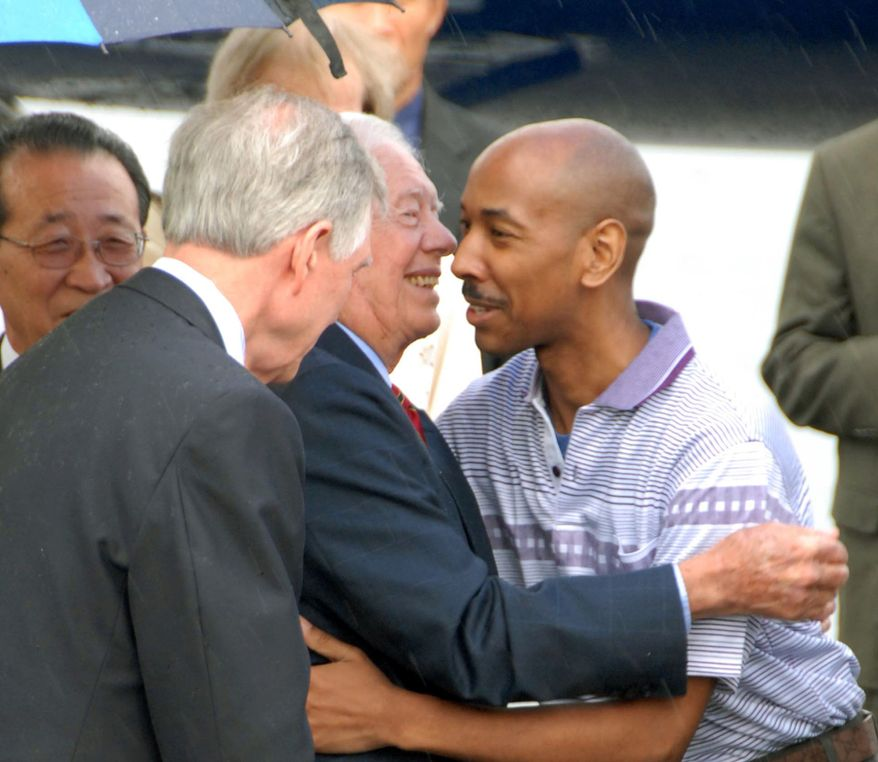 Former President Jimmy Carter, second left, and Aijalon Gomes, right, hugs as they prepare to leave North Korea from Pyongyang, on Friday Aug. 27, 2010. Mr. Gomes was freed after nearly seven months jailed in North Korea. (AP Photo/Kyodo News)