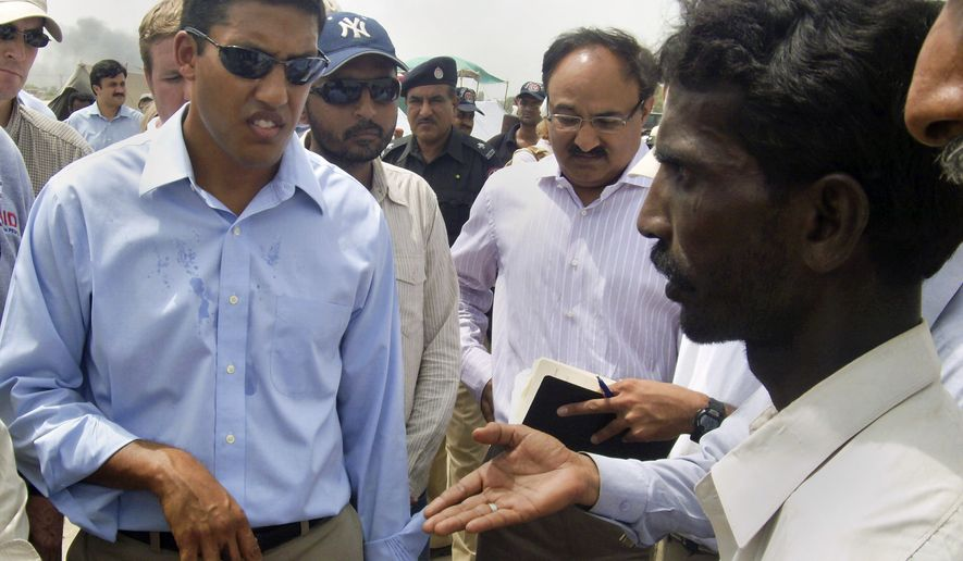 A Pakistani flood survivor interacts with Rajiv Shah, left, administrator of the U.S. Agency for International Development, during his visit to camp in Sukkur, Pakistan on Wednesday, Aug. 25, 2010. (AP Photo/Khurram Shahzad)