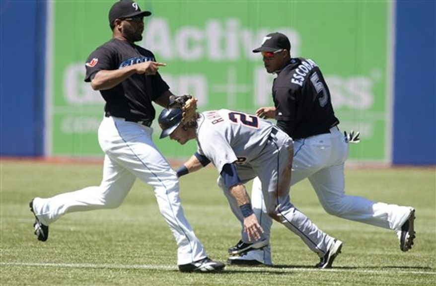 Detroit Tigers' Will Rhymes, center, is tagged out on a run down between Toronto Blue Jays' Edwin Encarnacion, left, nd Yunel Escobar during the first inning action of a baseball game in Toronto on Saturday, Aug. 28, 2010. (AP Photo/The Canadian Press, Chris Young)
