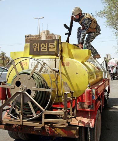 ON TOP OF IT: An Iraqi police officer searches a fuel tanker Sunday in Baghdad. Iraqi troops are poised to take over security, but some U.S. special operations forces will remain. (Associated Press)