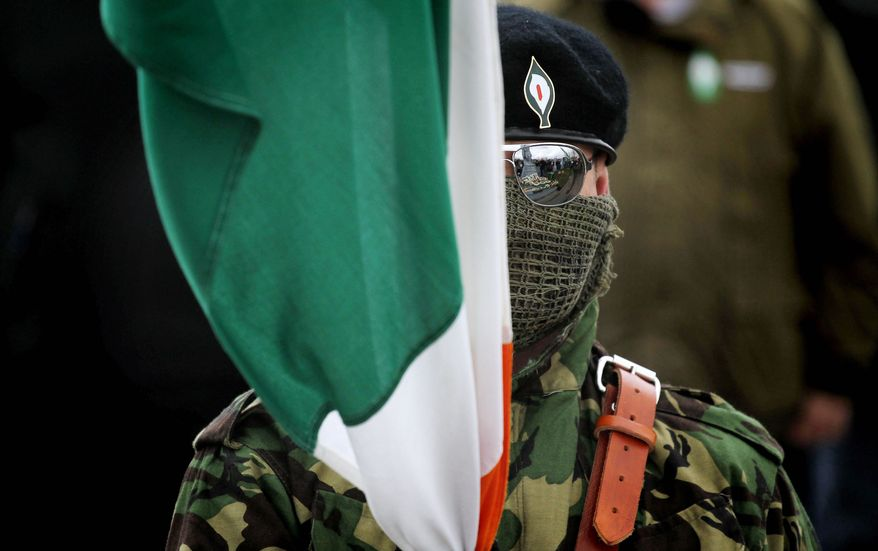 A member of the Real Irish Republican Army dissident group participates in a 1916 Easter rising commemoration ceremony at Creggan cemetery in Londonderry, Northern Ireland. (Associated Press)