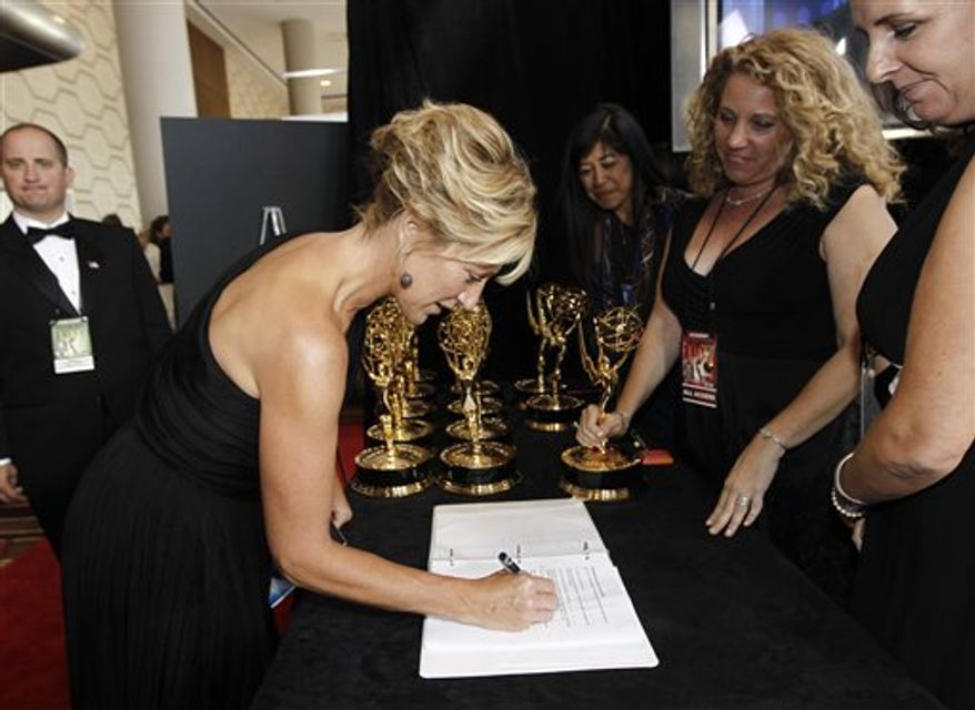 "Edie Falco picks up the best actress in a comedy series Emmy she won for her work on ""Nurse Jackie,"" backstage during the 62nd Primetime Emmy Awards Sunday, Aug. 29, 2010, in Los Angeles. (AP Photo/Matt Sayles)"