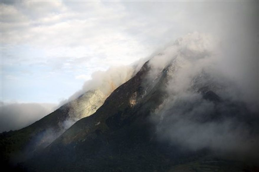 Mount Sinabung spews volcanic smoke in Karo, North Sumatra, Indonesia, Sunday, Aug. 29, 2010. The volcano spewed hot lava and sand high into the sky early Sunday in its first eruption in 400 years causing thousands of people living around its slope to evacuate their homes. (AP Photo/Binsar Bakkara)