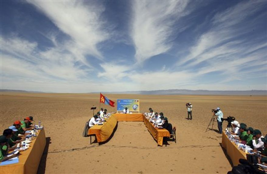"""In this photo taken Friday, Aug. 27, 2010 released by China's Xinhua News Agency, Mongolian Prime Minister Batbold Sukhbaatar answers questions during a Cabinet meeting aimed at drawing attention to climate change held in Gashuunii Khooloi, a sandy valley in South Gobi province, Mongolia. Top Mongolian officials donned dark green baseball caps reading """"Save our planet"""" and set up chairs and tables in the sands of the Gobi desert for the Cabinet meeting held in scorching heat Friday.  (AP Photo/Xinhua, Asigang)"""