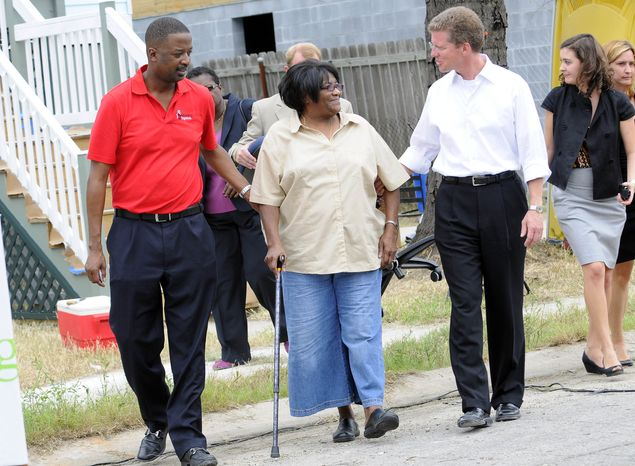 Gary Officer (left), CEO of Rebuilding Together, and Shaun Donovan (right), secretary of housing and urban development, escort homeowner Ruthie Lee Jones, whose home is one of 50 being rebuilt in five days by volunteers from around the country as part of Rebuilding Together's Fifty for Five in the Gentilly neighborhood of New Orleans on Thursday, Aug. 26, 2010. Ms. Jones has not been in her home since Katrina devastated the New Orleans and the Gulf Coast in 2005. (Cheryl Gerber/AP Images for Rebuilding Together)