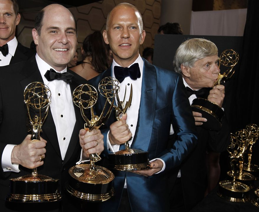 """""""Mad Men"""" creator Matthew Weiner (left) holds the best drama series award and director Ryan Murphy holds the best comedy series director award for """"Glee"""" backstage Sunday during the 62nd Primetime Emmy Awards in Los Angeles. Robert Morris (rear), from the cast of """"Mad Men,"""" kisses a trophy. (Associated Press)"""