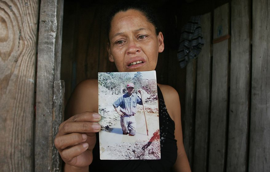 Marleni Xiomara Suarez Ortega, weeps as she speaks to the press while holding up a photo of her late husband, Miguel Angel Carcamo, outside of her home in Tegucigalpa, Honduras Saturday Aug. 28, 2010. Her husband purportedly was among the 72 migrants killed in northern Mexico by, what could be, a gang of drug traffickers.(AP Photo/Fernando Antonio)